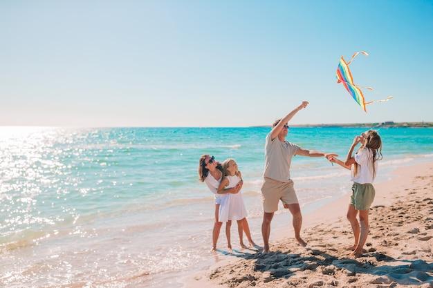 Glückliche junge familie mit zwei kindern, die einen drachen am strand fliegen