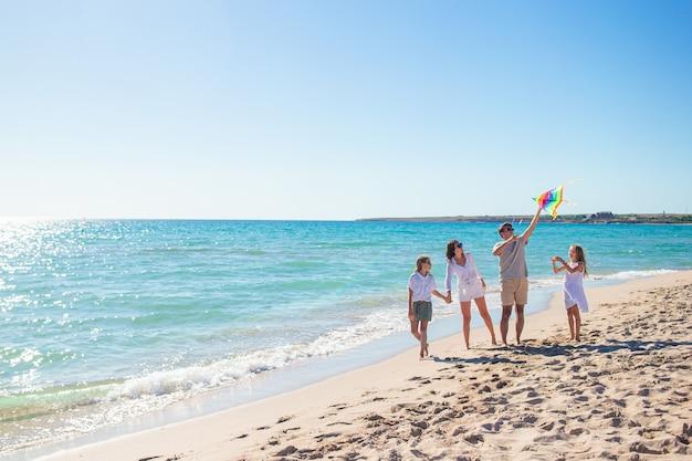 Glückliche junge familie mit zwei kindern mit dem drachenfliegen am strand