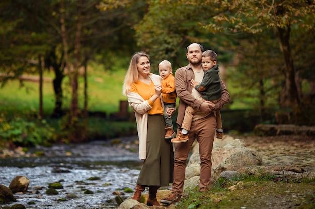 Glückliche junge familie mit zwei söhnen auf einem spaziergang im herbst im wald am fluss.