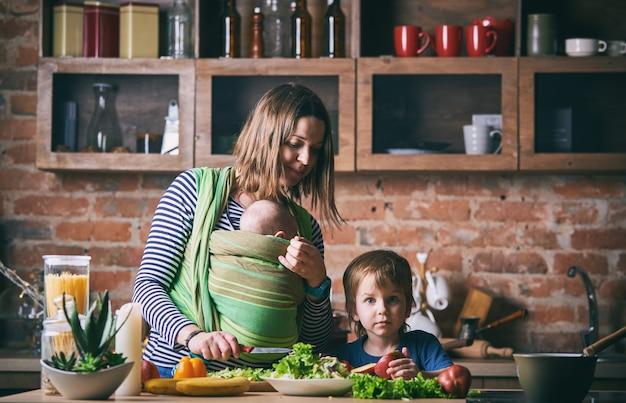 Glückliche junge familie, schöne mutter mit zwei kindern, entzückender vorschulkind und baby in der schlinge, die zusammen in einer sonnigen küche kocht.