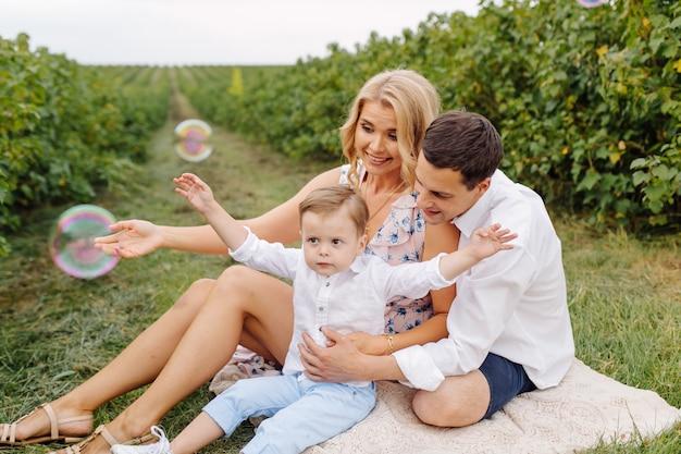 Glückliche junge familie vater, mutter und kleiner sohn sehen im park glücklich aus