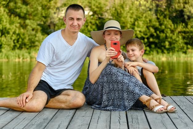 Glückliche junge familie, vater, mutter und zwei kleine söhne sitzen und machen selfies auf dem flusspier
