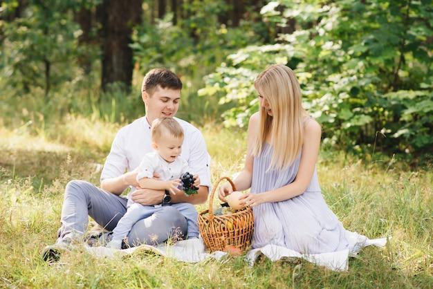 Glückliche junge familie verbringt zeit zusammen in der natur. picknick im wald