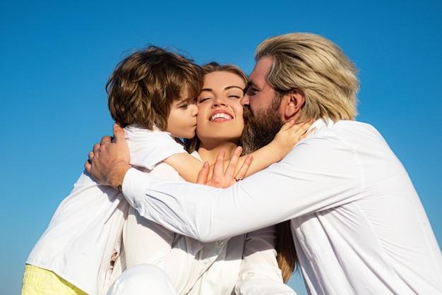 Glückliche junge familie verliebt sich draußen küssen.