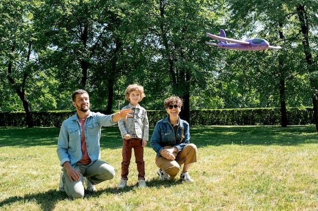 Glückliche junge familie von drei, die fliegendes spielzeugflugzeug beim zusammenspiel auf grünem rasen, umgeben von bäumen am sonnigen tag betrachten