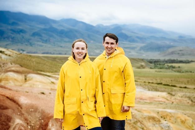 Glückliche junge familie von touristen mann und frau in gelb