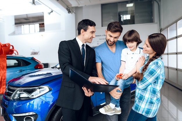 Glückliche junge familie wählen ein neues auto.