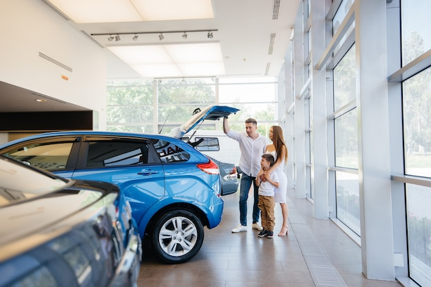 Glückliche junge familie wählt und kauft ein neues auto bei einem autohaus