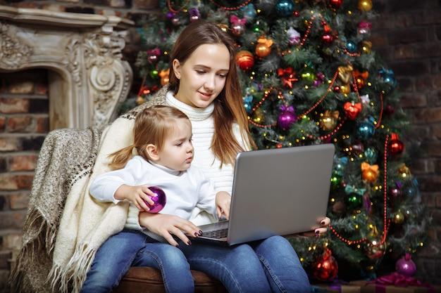 Glückliche junge familienmutter und -tochter, die einen laptop beim sitzen nahe dem weihnachtsbaum verwendet
