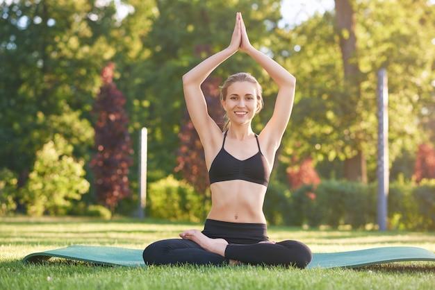 Glückliche junge fitnessfrau lächelnd freudig sitzend in lotussitz auf übungsmatte im freien im park yoga workout, das routine fit getöntes gesundheitskonzept ausübt.