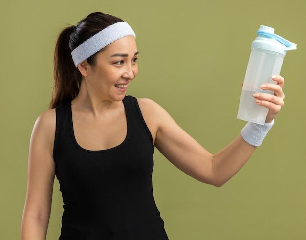 Glückliche junge fitnessfrau mit stirnband, die eine wasserflasche hält und sie mit einem lächeln auf dem gesicht betrachtet, das über der grünen wand steht?