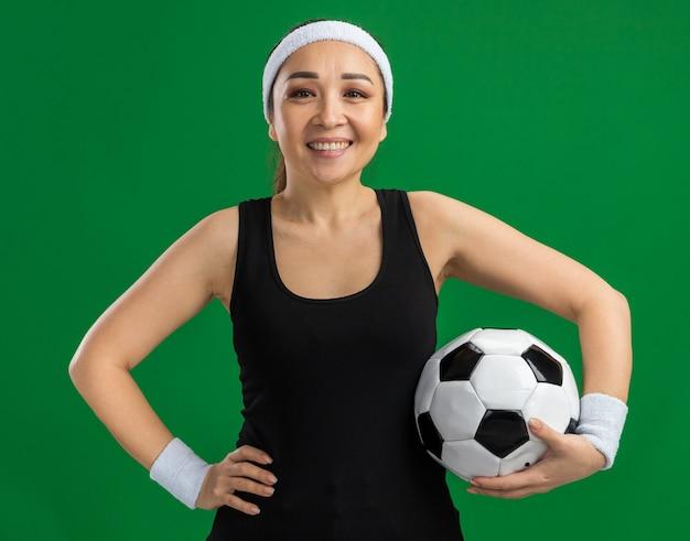 Glückliche junge fitnessfrau mit stirnband und armbinden, die fußball mit einem lächeln auf dem gesicht hält, das über grüner wand steht