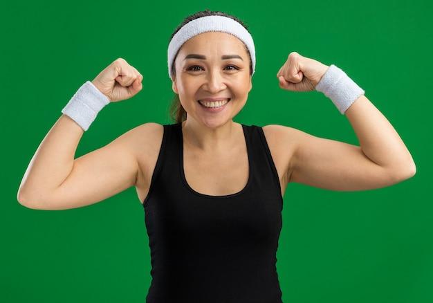Glückliche junge fitnessfrau mit stirnband und armbinden, die selbstbewusst lächelt und die fäuste hebt, die über grüner wand stehen