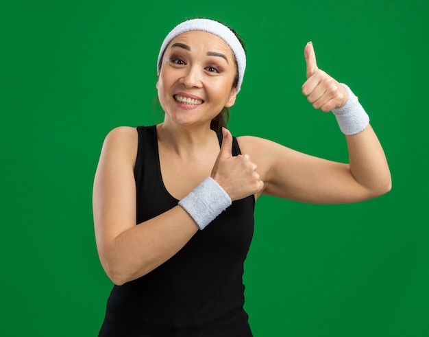 Glückliche junge fitnessfrau mit stirnband und armbinden mit einem lächeln im gesicht, das daumen nach oben über grüner wand zeigt