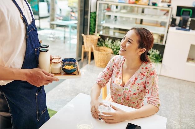 Glückliche junge frau am kaffeetisch