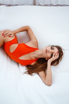 Glückliche junge frau am strand. outdoor-mode-porträt der glamour-dame, die ihren urlaub auf luxusvilla in der heißen tropischen insel genießt. sexy frau mit perfekter passform.