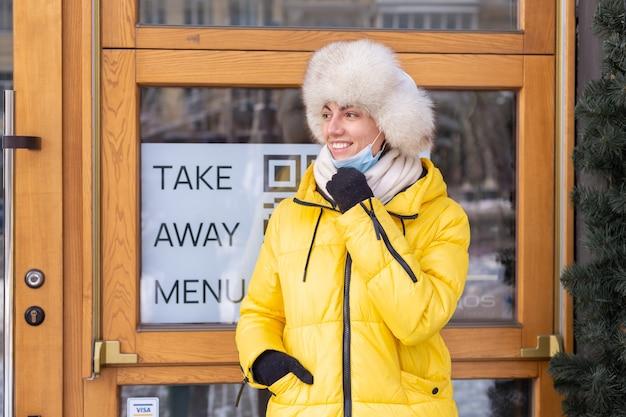 Glückliche junge frau an der tür des restaurants an einem kalten wintertag, schriftzug, essen zum mitnehmen.