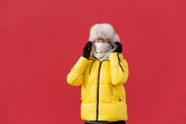 Glückliche junge frau auf dem hintergrund einer roten wand in warmen kleidern an einem sonnigen wintertag