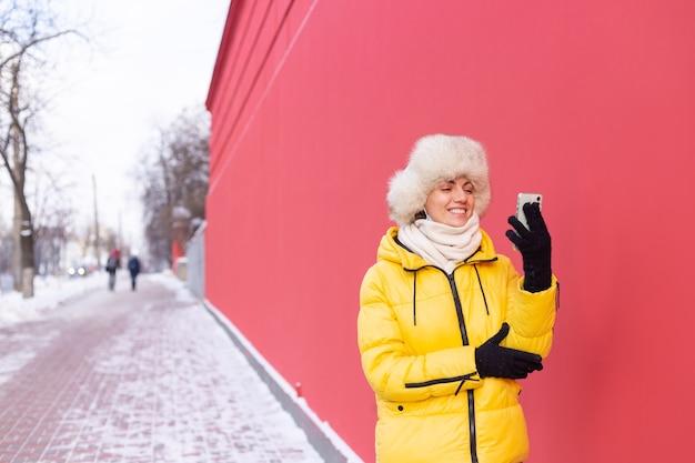 Glückliche junge frau auf einem hintergrund einer roten wand in warmen kleidern an einem sonnigen wintertag lächelnd und am telefon auf einem schneebedeckten stadtbürgersteig sprechend