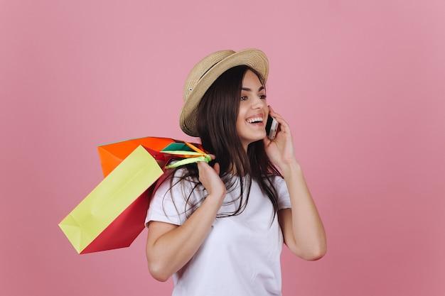 Glückliche junge frau benutzt ihr telefon, das mit bunten einkaufstaschen im studio aufwirft