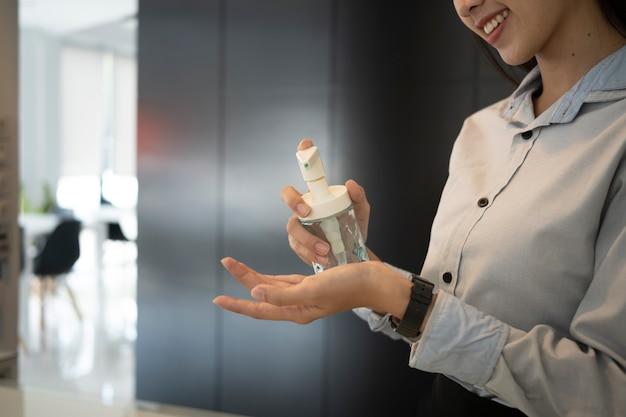 Glückliche junge frau, die alkohol-desinfektionsgel auf ihrer hand anwendet