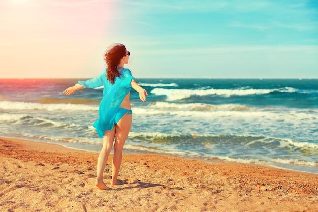 Glückliche junge frau, die am strand spazieren geht