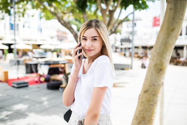 Glückliche junge frau, die am telefon am stadtstraßenlebensstilporträt in der sommerzeit spricht