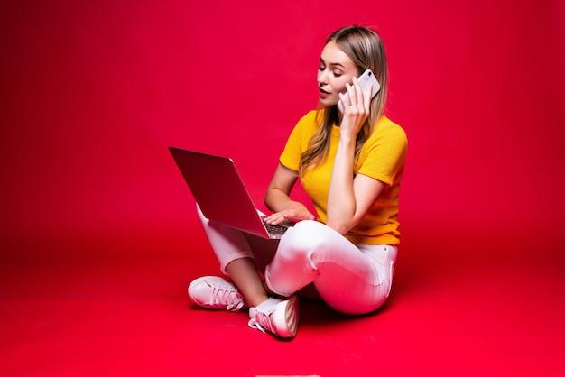 Glückliche junge frau, die am telefon mit gekreuzten beinen auf dem boden sitzt und laptop auf roter wand verwendet.
