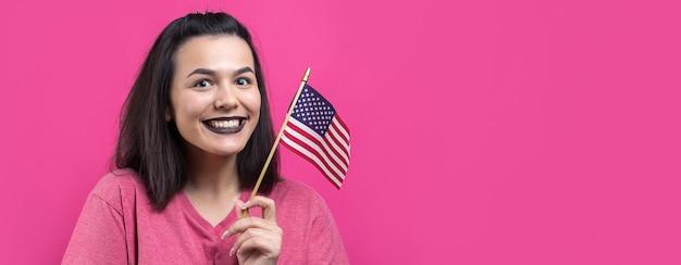 Glückliche junge frau, die amerikanische flagge gegen einen rosafarbenen hintergrund des studios hält