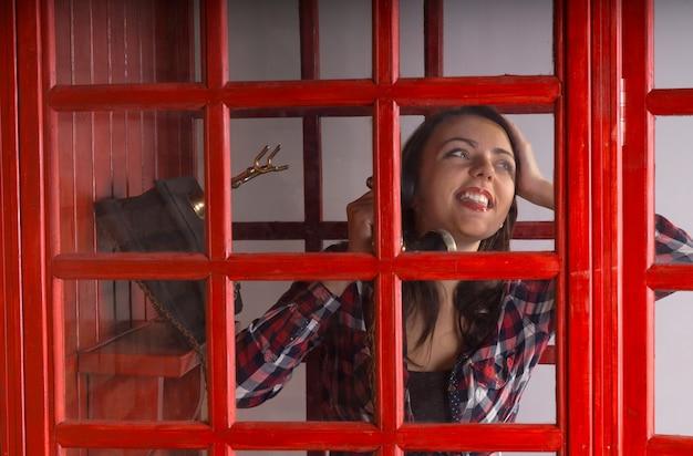 Glückliche junge frau, die an einem öffentlichen telefon in einer roten telefonzelle plaudert und vor freude lächelt, während sie dem gespräch zuhört