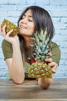 Glückliche junge frau, die ananas auf blauer oberfläche hält