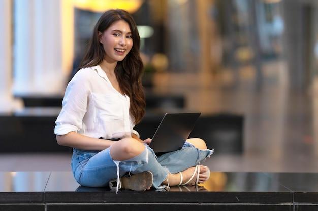 Glückliche junge frau, die auf dem boden mit laptop in der nacht auf stadt sitzt