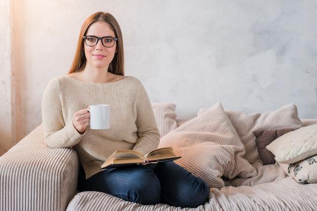 Glückliche junge frau, die auf dem sofa hält buch und tasse kaffee in den händen sitzt