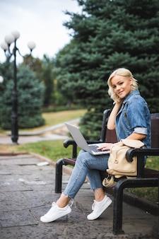 Glückliche junge frau, die auf der bank sitzt und telefon und laptop im herbstmorgen der stadt benutzt