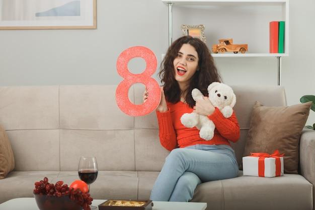 Glückliche junge frau, die auf einer couch mit nummer acht sitzt und teddybär und geschenk hält. wir feiern den internationalen frauentag