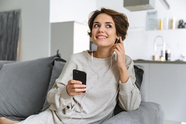 Glückliche junge frau, die auf einer couch zu hause sitzt, mit handy, musik mit kopfhörern hörend