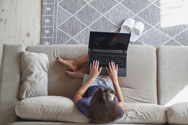 Glückliche junge frau, die auf sofa sitzt und laptop zu hause benutzt
