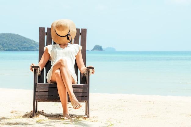 Glückliche junge frau, die auf strandkorb am tropischen strand im weißen kleid sitzt. das leben genießen, sorglos, entspannte sommerstimmung