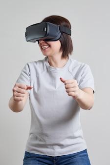 Glückliche junge frau, die auf vr-brille im innenbereich spielt, virtual-reality-konzept mit jungem mädchen, das spaß mit headset-brille hat