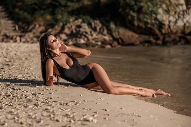 Glückliche junge frau, die auf weißem sand liegt und für die kamera aufwirft.