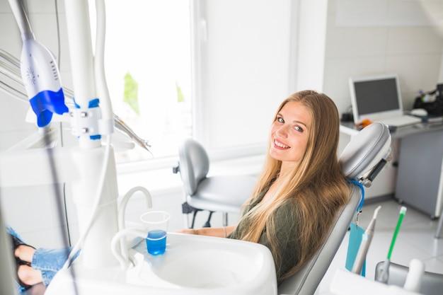 Glückliche junge frau, die auf zahnmedizinischem stuhl sitzt