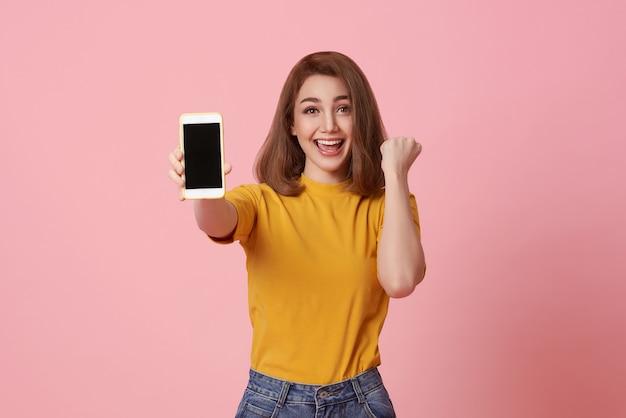 Glückliche junge frau, die bei leerem bildschirm-handy und handgestenerfolg einzeln auf rosa hintergrund zeigt.