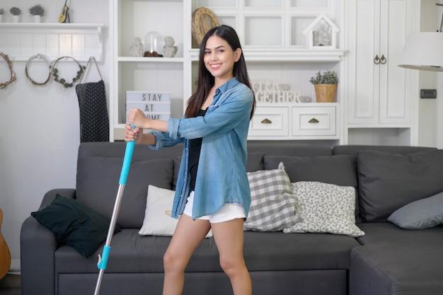 Glückliche junge frau, die boden mit mopp im wohnzimmer säubert
