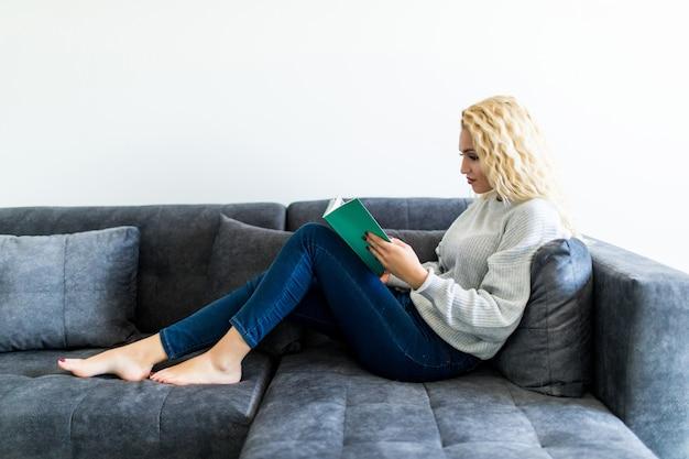 Glückliche junge frau, die buch auf couch zu hause liest