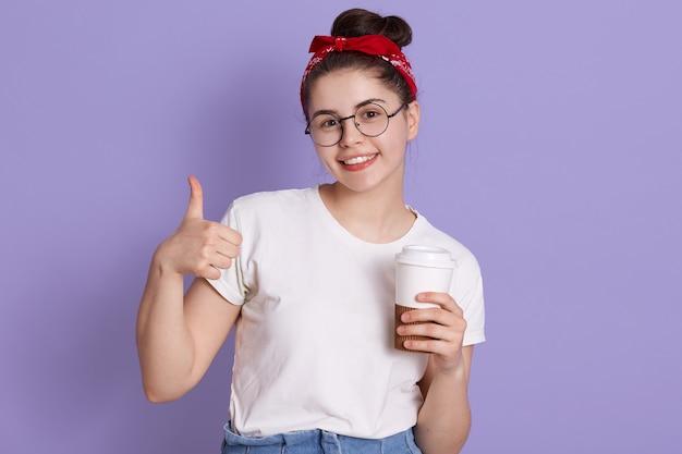 Glückliche junge frau, die daumen oben zeigt und kaffee zum mitnehmen hält und direkt in die kamera lächelt und freizeitkleidung und rotes haarband trägt