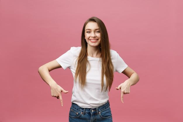 Glückliche junge frau, die den finger lokalisiert über rosa hintergrund steht und zeigt