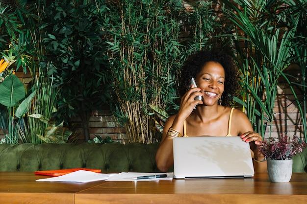Glückliche junge frau, die den laptop bei der unterhaltung auf mobiltelefon schließt