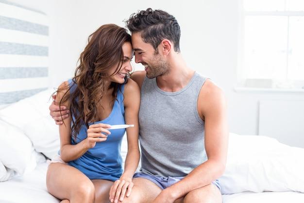 Glückliche junge frau, die den schwangerschaftstest sitzt neben ehemann hält