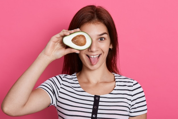 Glückliche junge frau, die die hälfte der avocado hält, ihr auge mit gesunden früchten bedeckt, ihre zunge zeigt, gestreiftes t-shirt trägt, isoliert über rosa wand aufwirft.
