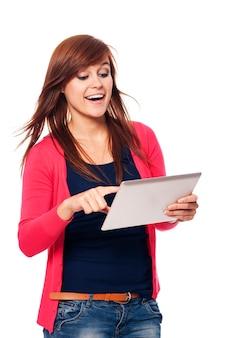 Glückliche junge frau, die digitales tablett verwendet
